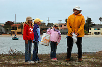 Mariner's Point, San Diego, CA, USA.  Saturday, December 13, 2008:  Kids Korps Volunteers from Point Loma's Explorer Elementary School; Sydney Fortune (2nd Grade), Ciara Gray (3rd Grade) and Shelby Fortune (K) work with Chet Nelson to clean up one of the last Least Tern nesting sites on Mission Bay.