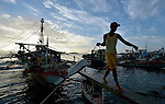 Workers unload fish at sunrise from boats in the harbor of Estancia, a village in the Philippines that was hit hard by Typhoon Haiyan in November 2013. The storm was known locally as Yolanda. The ACT Alliance has been active assisting residents of this town to recover from the typhoon.