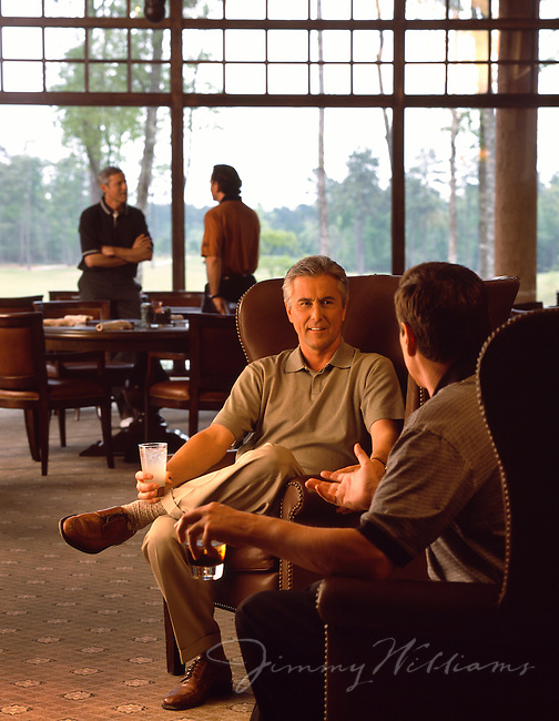 Two men sit and have drinks together at a private Country Club & Golf Resort