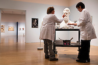 """Conservators Rika Smith McNally (right) and Regina Gaudette work on a replacement nose for a bust of abolitionist John Brown in the Tisch Family Gallery at the Tufts University Art Gallery at Tufts University in Medford, Massachusetts, on Thurs., Oct. 6, 2016. The bust was sculpted by Edward Augustus Brackett and had been improperly stored for decades with a broken nose and eyebrow. The conservators, from Rika Smith McNally and Associates, found a plaster cast made from the original at the Boston Athenæum and had a 3D modeler image the broken section of the original and the cast. They then used 3D printing technology to use to create a plaster nose replacement that would fit perfectly on the broken marble bust. They then used gouache paint to match the replacement pieces to the original marble.  The bust is part of an exhibition at the gallery entitled """"Mortal Things: Portraits Look Back and Forth."""""""