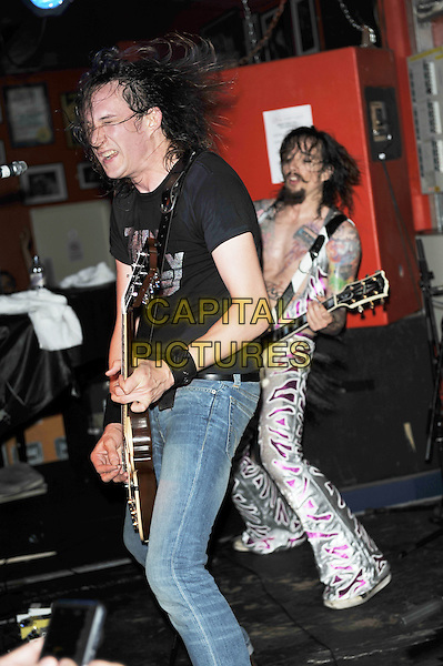 Dan and Justin Hawkins.The Darkness live in concert, 100 Club, London, England. .10th October 2011.on stage performance performing music gig full length tattoos guitar black grey gray white print goatee moustache mustache facial hair spandex jumpsuit t-shirt jeans denim side pink silver.CAP/MAR.© Martin Harris/Capital Pictures.