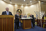 L-R, Rabbit CHARLES KLEIN, Nassau County Executive ED MANGANO, New York Senator-Elect MICHAEL VENDITTO, Assemblyman DAVE McDONOUGH, Assistant Rabbi RAVID TILLES, and others, participate in the ceremonial candle lighting on the bema in the main sanctuary of the Merrick Jewish Centre, when it attempts to regain the Guinness World's Record for Most Menorot Lit in One Place at One Time that the congregation held in 2011. On the third night of Hanukkah, the 'Light Up the Night 2 - Bringing the Record Home' event also included bagpipers.