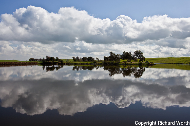Sky, clouds and trees reflected in Bethany Reservoir near Livermore, California.