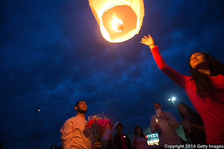 BURLINGTON, WA - SEPTEMBER 26: Soledad Lara (right) lets go of a light lantern during a candlelight vigil outside the Cascade Mall on September 26, 2016 in Burlington, Washington. Five people were killed in the Macy's department store behind them by a gunman several night's ago. Among the dead was Lara's sister, Sarai. The suspect, Arcan Cetin, 20, a resident of Oak Harbor, Washington, was arraigned today. (Photo by Karen Ducey/Getty Images)