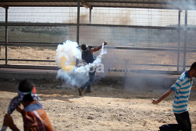 A Palestinian protester throws back a tear gas canister during clashes with Israeli security forces next to the border fence with Israel, at the Erez crossing in the northern Gaza strip, on October 13, 2015. A wave of stabbings that hit Israel, Jerusalem and the West Bank this month along with violent protests in annexed east Jerusalem and the occupied West Bank, has led to warnings that a full-scale Palestinian uprising, or third intifada, could erupt. The unrest has also spread to the Gaza Strip, with clashes along the border in recent days leaving nine Palestinians dead from Israeli fire. Photo by Ashraf Amra