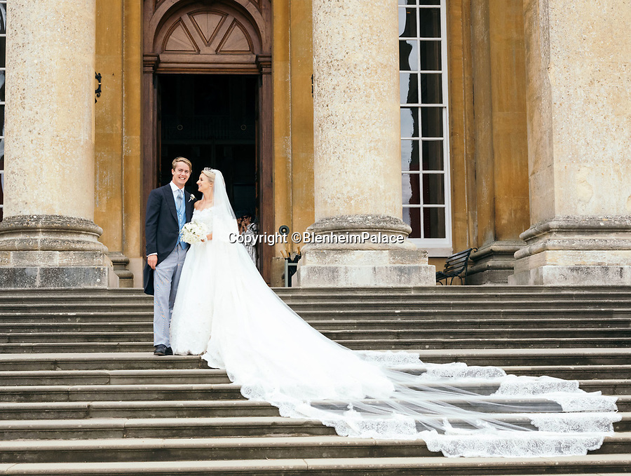 BNPS.co.uk (01202 558833)<br /> Pic: BlenheimPalace<br /> <br /> Lord and Lady Blandford on their wedding day last year.<br /> <br /> The stunning wedding dress worn by Camilla Thorp on her marriage to Lord George Blandford, heir to the Duke of Marlborough, has just gone on display at Blenheim Palace in Oxfordshire.<br /> <br /> The first bespoke Dolce & Gabbana bridal gown ever to have been worn in Britain, Lady Blandford made several visits to the Milan fashion house prior to her lavish September wedding last year.<br /> <br /> The dress, which is on display in the Palace's Long Library, features an off-the-shoulder lace bodice with tiny, pale pink and white appliqued flowers and seed pearls. <br />