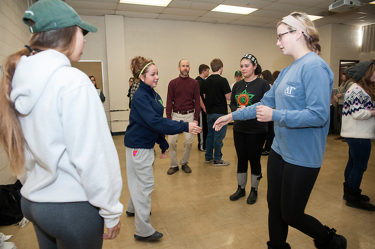 Students Alexa Johnson and Mackenzie Tracy reach out to each other while trying to solve a math problem with contradance during their mathematics for educators class on Friday, February 13.