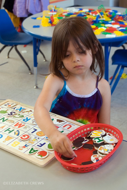 Berkeley CA  Four-year-old preschool student working on alphabet puzzle in class