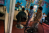 A Salvadoran hairdresser cuts a man's hair in a barber shop in San Salvador, El Salvador, 10 April 2018.