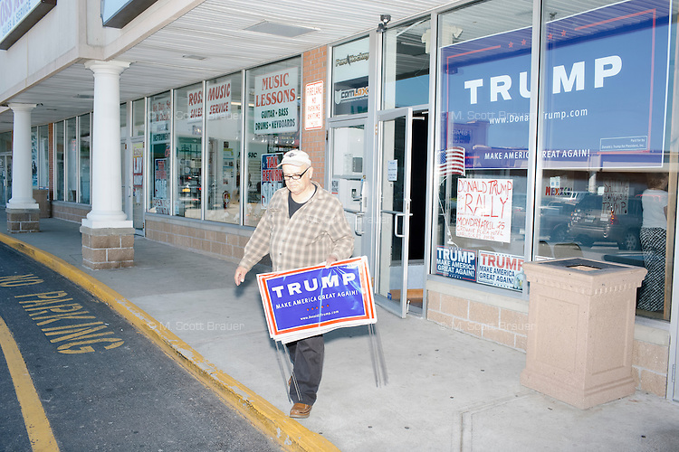 """Trump supporter Richard Lempitsky, of Cumberland, Rhode Island, carries signs out of the Rhode Island state campaign headquarters for Republican presidential candidate Donald Trump at the Airport Plaza strip mall in Warwick, Rhode Island, USA, on Sun., Apr. 24, 2016. The campaigns of Trump, Cruz, and Kasich, have all set up offices in the strip mall. Lempitsky said, """"I've been a Republican all my life. Since Goldwater."""""""