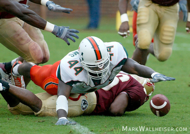 Miami's Leon Williams (44) dives over FSU's Ray Piquion (56) going after a punt that Miami blocked in the first half against Florida State in the pouring rain in Tallahassee October 11, 2003.