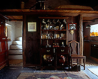 The two-stage cupboard to the right of a rustic staircase in the living area was a predecessor of the dresser