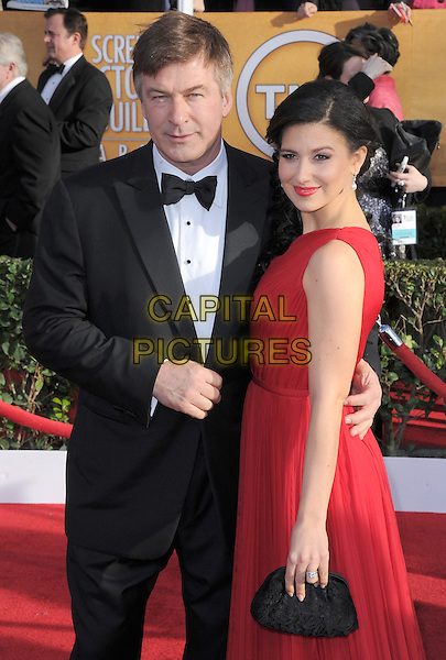 Alec Baldwin & Hilaria Thomas.Arrivals at the 19th Annual Screen Actors Guild Awards at the Shrine Auditorium in Los Angeles, California, USA..27th January 2013.SAG SAGs half length black tuxedo bow tie red one shoulder dress married husband wife clutch.CAP/DVS.©DVS/Capital Pictures.