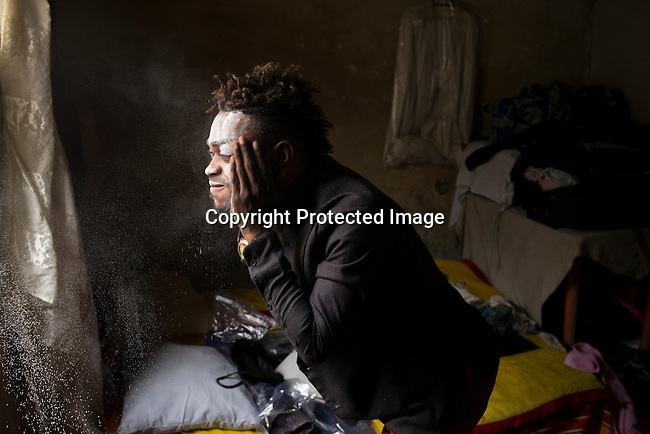 """KINSHASA, DEMOCRATIC REPUBLIC OF CONGO - OCTOBER 3: Mzee Kindingu, the leader of the Sapeurs group The Leopards powders his face after taking a bath,  in his bedroom on February 3, 2015 in Kinshasa, DRC. The word Sapeur comes from SAPE, a French acronym for Société des Ambianceurs et Persons Élégants. or Society of Revellers and Elegant People. and it also means, .to dress with elegance and style"""". Most of the young Sapeurs are unemployed, poor and live in harsh conditions in Kinshasa, a city of about 10 million people. For many of them being a Sapeur means they can escape their daily struggles and dress like fashionable Europeans. Many hustle to build up their expensive collections. Most Sapeurs could never afford to visit Paris, and usually relatives send or bring clothes back to Kinshasa. (Photo by Per-Anders Pettersson)"""