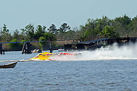 Frame 2: Terry Rinker (#10) and Chris Fairchild (#62) race up the back stright to turn 2 where Rinker's boat rolls over a wake, noses in and flips.   (Formula 1/F1/Champ class)