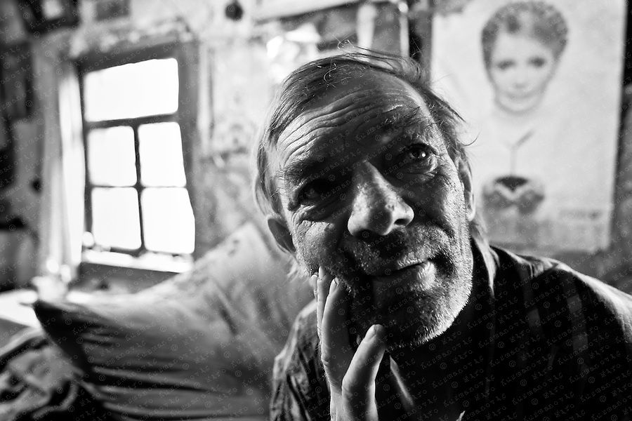 Fedir Fedorovicz, 52, sits in his home in the abandoned village of Ilintsy, as a poster of Prime Minister Yuliya Timoshenko is seen in the back. Fedir, one of the two inhabitants of Ilintsy, never left the exclusion zone near Prypiat.