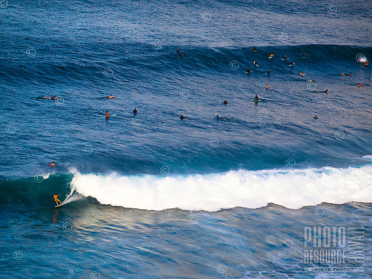 Woman surfer rides a wave while others wait at Honolua Bay, Maui.