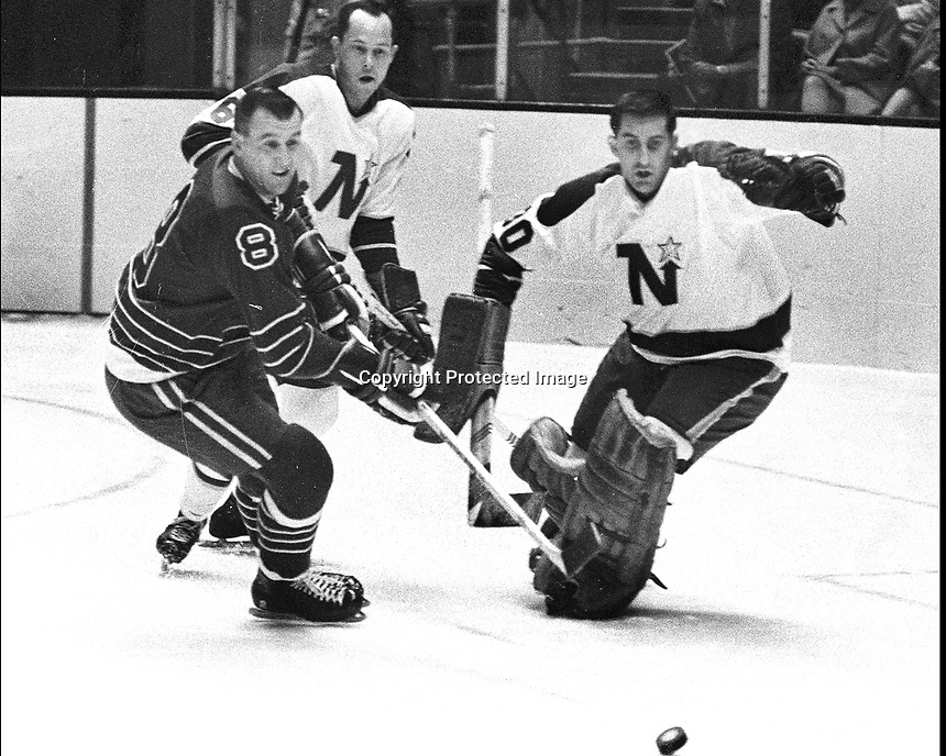 Seals vs the North Stars 1967,Gerry Ehman #8.tries to score on goalie Cesare Maniago, and Mike McMahon. (photo/Ron Riesterer).
