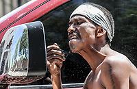 Un pandilleroutiliza un espejo retrovisor de una camioneta para rasurare la barba.
