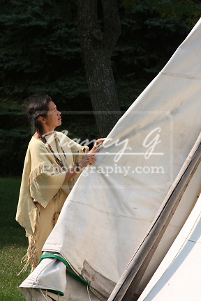 Native American Indian woman breaking down a tipi to move