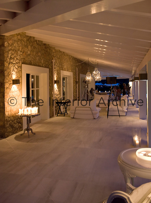 Smooth, marble floor tiles pave the way to a  seating area under the covered terrace, the white surfaces reflecting the warm glow of candlelight