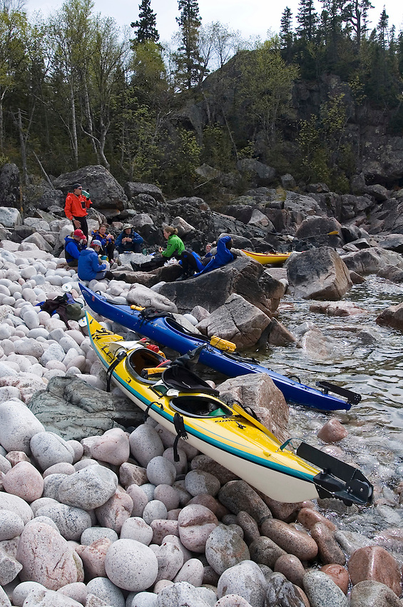 A group of sea kayakers rest and eat lunch on a cobblestone beach in Lake Superior Provincial Park near Wawa Ontario Canada.