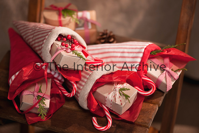 A group of cheerful red and white Christmas cones are filled with small presents and candy canes