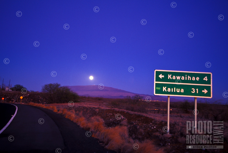 Moonrise over Hualalai peak with street sign for Kawaihae and Kailua turns,taken from  Puako  area