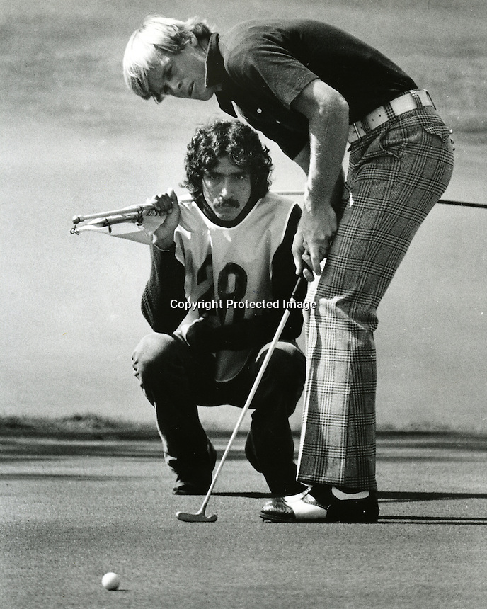Johnny Miller has his caddy check his aim while putting..(copyright 1975 Ron Riesterer)