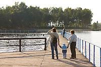 People enjoying the dock walkway over the lake at the city park. Rawa Mazowiecka Central Poland