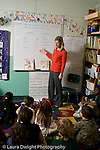 Education Elementary school Grade 2 English language arts female teacher using dry erase board to put up Venn diagram to illustrate concept to class which is sitting on rug vertical