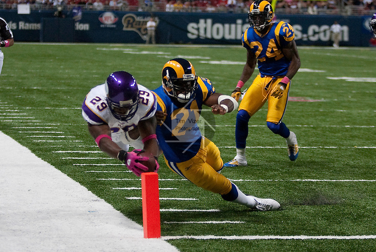 October 11, 2009         Vikings RB Chester Taylor (29, left) was trying to dive into the end zone for the TD, but Rams safety Oshiomogho Atogwe (21, right) jumped into him, forcing him out of bounds just short of the end zone.  The play was late in the game.  Also shown is Rams player Ron Bartell (24, right).     The Minnesota Vikings defeated the St. Louis Rams at the Edward Jones Dome in downtown St. Louis, Missouri, by a score of 38-10..