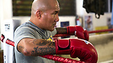 USA, Oahu, Hawaii, a gym owner takes a rest during boxing training in Honolulu