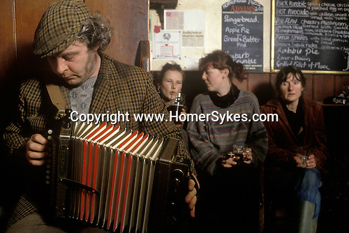 Man farmer playing the accordion in village pub The Kings Head, Low House, Laxfield Suffolk, UK.