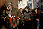 Man farmer playing a melodeon in village pub The Kings Head, Low House, Laxfield Suffolk, UK.