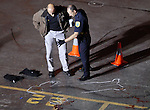 Green Bay police Lt. Todd Thomas, left, and officer Eric Allen survey the chalk outline of a man shot and killed in the Pi nightclub parking lot around 1 a.m. on October 13, 2006.