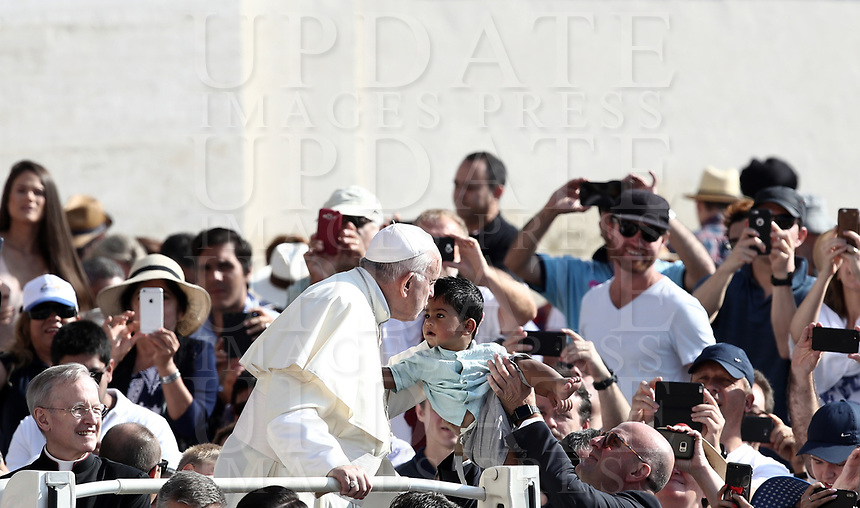Papa Francesco bacia un bambino al suo arrivo all'udienza generale del mercoledi' in Piazza San Pietro, Citta' del Vaticano, 29 agosto, 2018.<br /> Pope Francis kisses a child as he arrives to lead his weekly general audience in St. Peter's Square at the Vatican, on August 29, 2018.<br /> UPDATE IMAGES PRESS/Isabella Bonotto<br /> <br /> STRICTLY ONLY FOR EDITORIAL USE