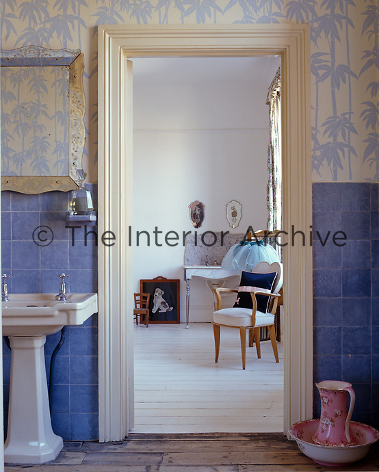 "The Broadhurst 'Bamboo"" wallpaper blends with the blue ceramic wall tiles in this original 1930s bathroom"