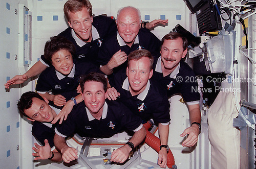 With their feet anchored in the hatchway, the seven STS-95 crew members pose for their traditional in-flight crew portrait. Astronaut Curtis L. Brown Jr., commander, appears at right center in the pyramid. Others, clockwise from there, are Steven W. Lindsey, pilot; Stephen K. Robinson, mission specialist; Pedro Duque, mission specialist representing the European Space Agency (ESA); payload specialist Chiaki Naito-Mukai, who represents Japan's National Space Development Agency (NASDA); Scott E. Parazynski, mission specialist; and United States Senator John H. Glenn Jr. (Democrat of Ohio), payload specialist..Credit: NASA via CNP