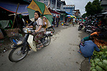 A woman and her child ride a motorcycle through the Tahan Market in Kalay, a town in Myanmar. This market is located in Tahan, the largely ethnic Chin section of the town.