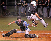 Swansboro catcher tags out Topsiail runner as he attempts to out jump the catchers glove at homeplate.