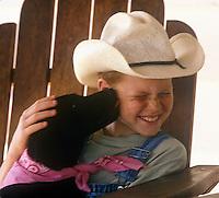 Boy being licked by black Labrador retriever puppy.