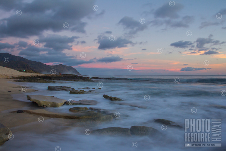 A long exposure image after sunset captures the movement of the waves along the shore of West O'ahu.