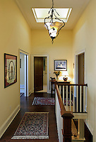 Traditional second floor hallway and staircase with custom Lalique style chandelier, skylight and stair rail,
