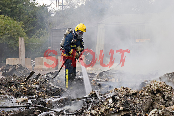 Firefighters wearing BA damping down the remains of a severe fire at an Industrial Unit Warwickshire UK. This image may only be used to portray the subject in a positive manner..©shoutpictures.com..john@shoutpictures.com