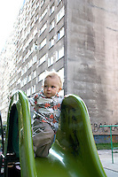 Apprehensive toddler on park slide. Blok housing behind a reminder of the communist era. Balucki District Lodz Central Poland