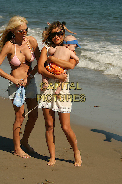 CARMEN ELECTRA & LYRICK LONDON (HER GODSON).Carmen Electra relaxes and enjoys the surf at the Polaroid Beach House, Malibu, California, USA..August 12th, 2007.full length sunglasses shades white cream dress carrying child infant blue hat visor .CAP/ADM/RE.©Russ Elliot/AdMedia/Capital Pictures