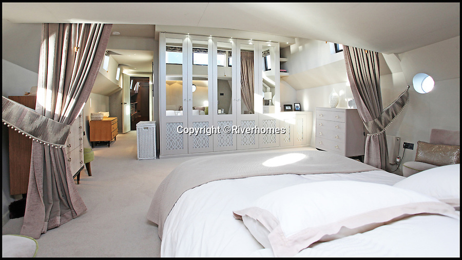 BNPS.co.uk (01202 558833)<br /> Pic: Riverhomes/BNPS<br /> <br /> Palatial main bedroom.<br /> <br /> Heart of Lightness - Tardis like houseboat on the Thames.<br /> <br /> A houseboat that looks more like a luxurious penthouse suite inside has gone on the market for a whopping &pound;1.5 million - because it's in one of London's most exclusive locations.<br /> <br /> The 100ft vessel was once a former Dutch barge taking supplies up and down the Thames until it was retired from service in the 1960s and left to rot.<br /> <br /> But a decade later it was salvaged and turned into a houseboat before undergoing a complete refurbishment four years ago and moved to a premier mooring alongside one the swankiest addresses in the city.<br /> <br /> The plush houseboat, berthed at the entrance to Cheyne Walk, now boasts a lavish living room, stylish 50ft-long kitchen, a spiral staircase, two opulent bedrooms, three bathrooms and even a sun terrace.<br /> <br /> And despite its eye-watering &pound;1.5m asking price, experts at Riverhomes estate agents say the houseboat is actually a bargain and that anyone wanting to live in such luxury in the heart of Chelsea would have to shell out many millions more.