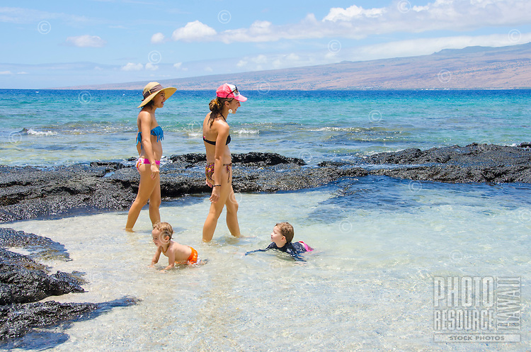Two local mothers walk in a tidal pool with their children playing nearby, Puako, South Kohala, Big Island.