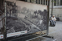 A disabled man sits in his wheelchair at the side of an old picture showing a destroyed town centre of Leuven during World War I, in Leuven, Flemish Brabant, Belgium, August 25, 2014. 2014 marks 100th anniversary of the Great War.